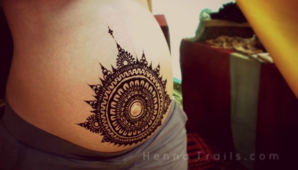 Her prenatal belly mandala henna design, first thing in the morning on the festival grounds.
